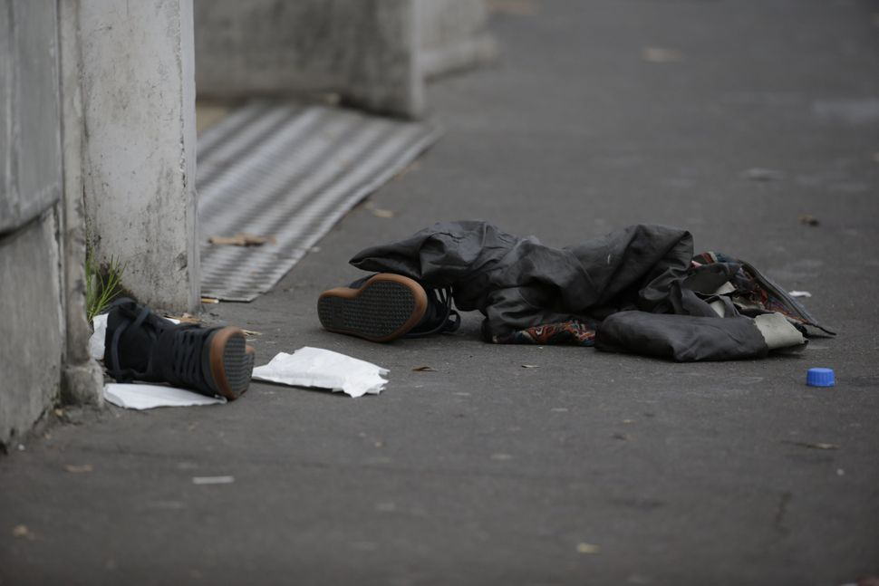 Personal items believed to belong to a fleeing concertgoer lie on the pavement near the Bataclan theatre in the 11th district