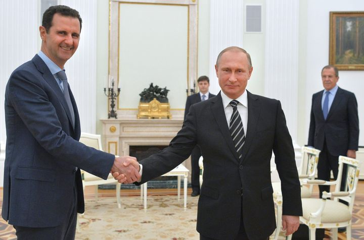 Russian President Vladimir Putin (R) shakes hands with his Syrian counterpart Bashar al-Assad (L) during a meeting at the Kre