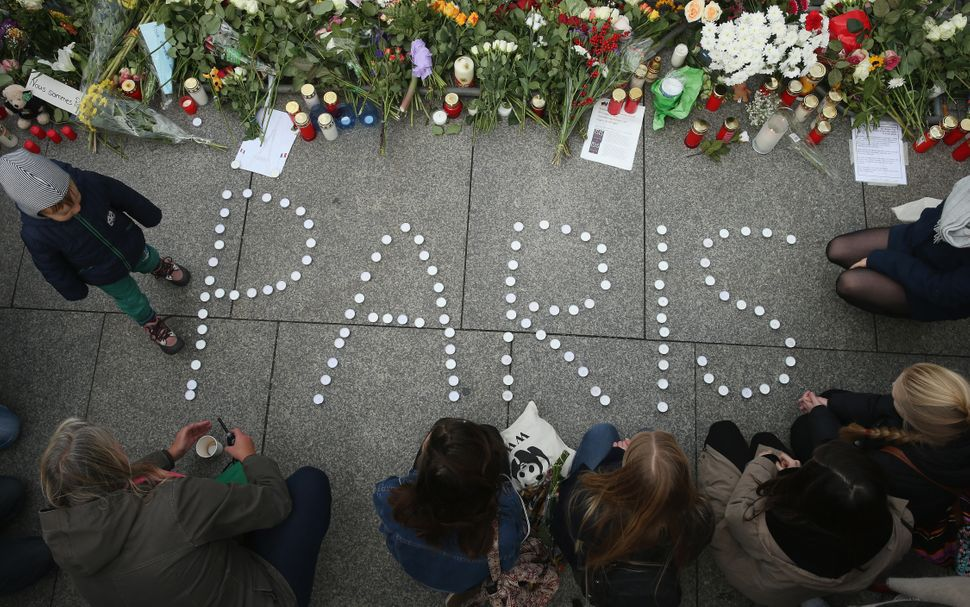 "People finish arranging candles into the word ""Paris"" next to flowers and messages left at the gate of the French Embassy fol"