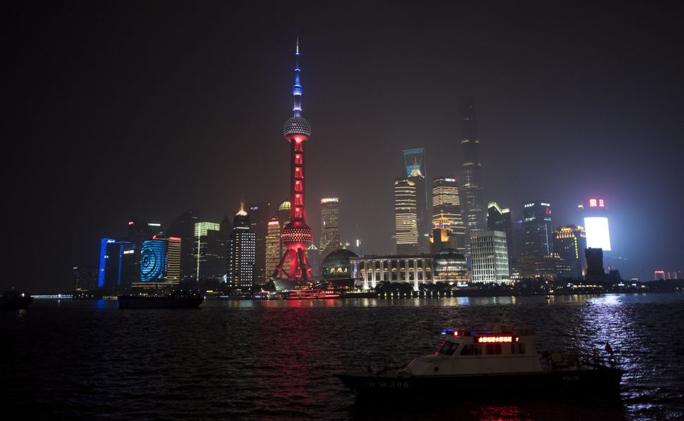 The Oriental Pearl TV Tower (center), in the Lujiazui Financial District in Pudong, is lit in the colors of the French flag,