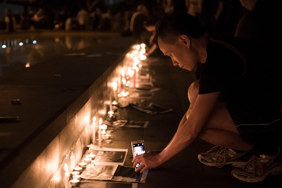 A man takes a picture of candles during a memorial event for victims of the Paris terror attacks on Nov. 14, 2015 in Hong Kon
