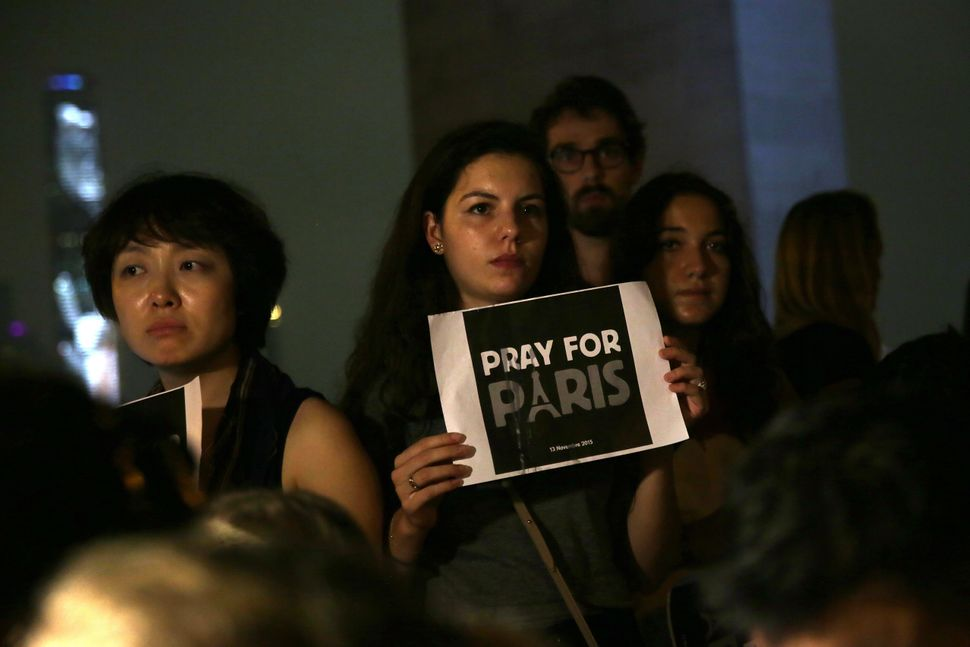 A woman holds a sign that reads 'Pray for Paris' during a vigil for victims of the French terror attacks at Sun Yat Sen Memor