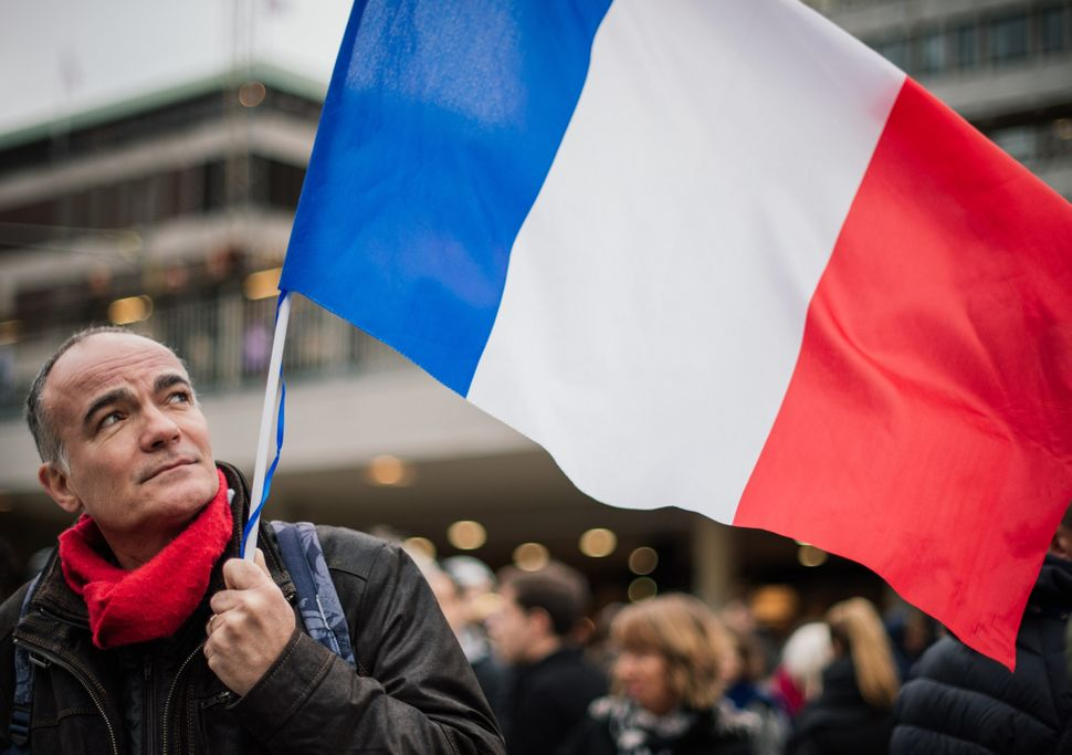 A man holds a French flag during a solidarity gathering in Stockholm a day after deadly attacks in Paris on Nov. 14, 201