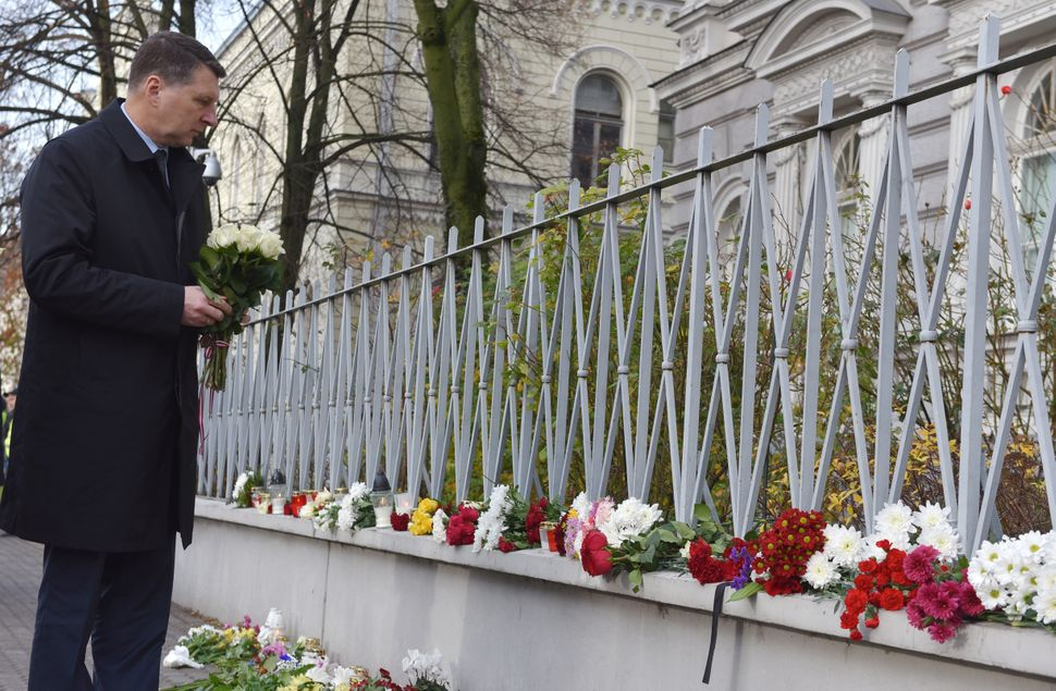 Latvian President Raimonds Vejonis places flowers in front of the French embassy in Riga, Latvia, on Nov. 14, 2015.