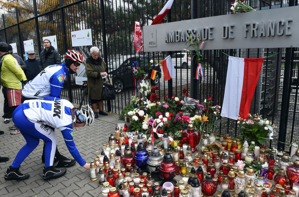 People lay flowers and light candles in front of the French Embassy in Warsaw, Poland, on Nov. 14, 2015.