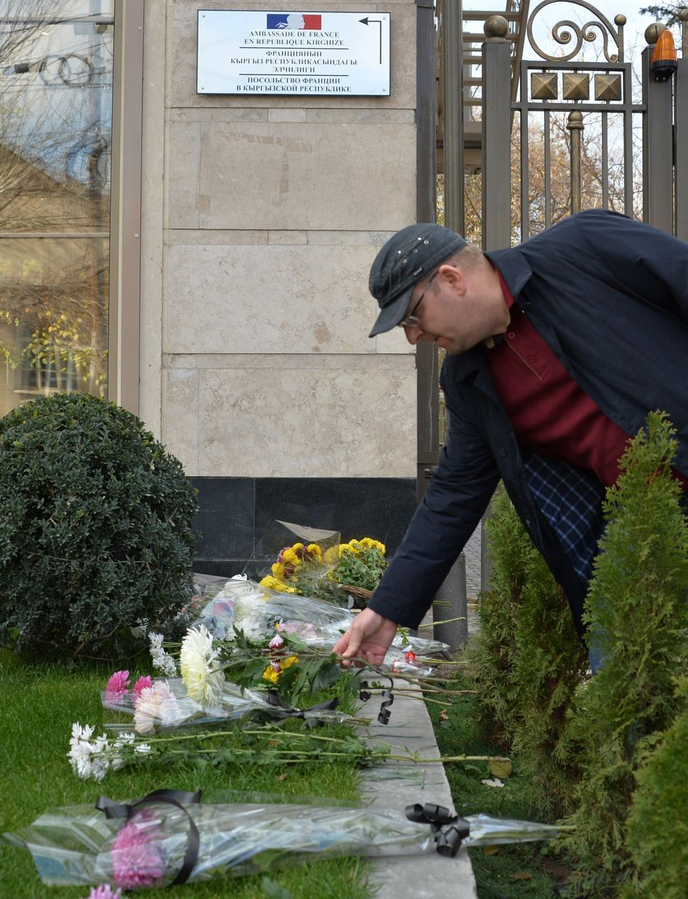 A man places flowers outside the French embassy in Bishkek, Kyrgyzstan, on Nov. 14, 2015.