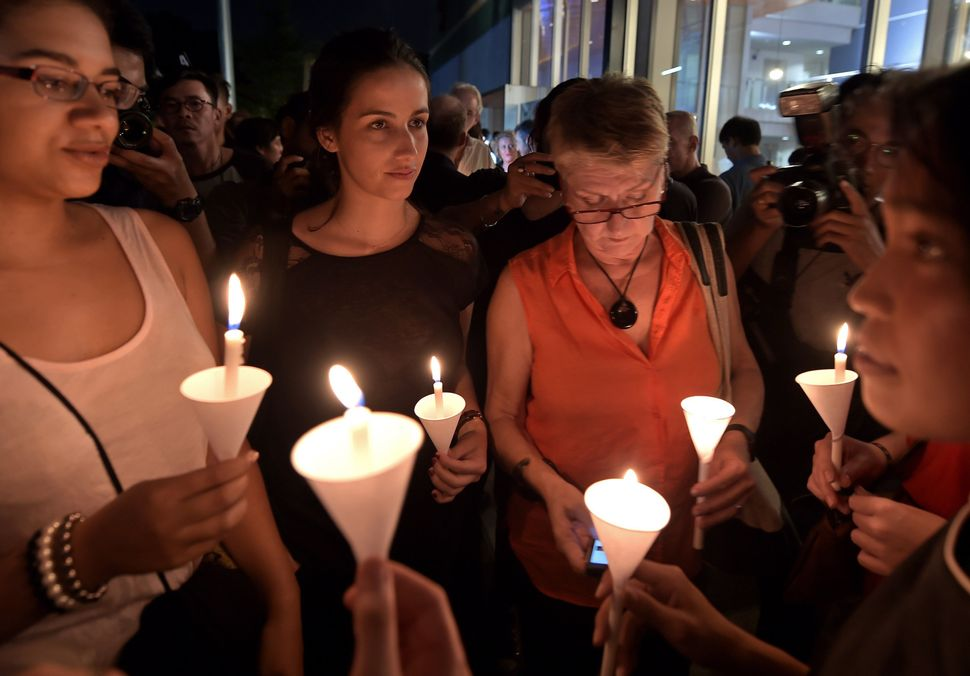 French nationals hold candles during a vigil at the Alliance Francaise in the Thai capital Bangkok on Nov. 14, 2015.
