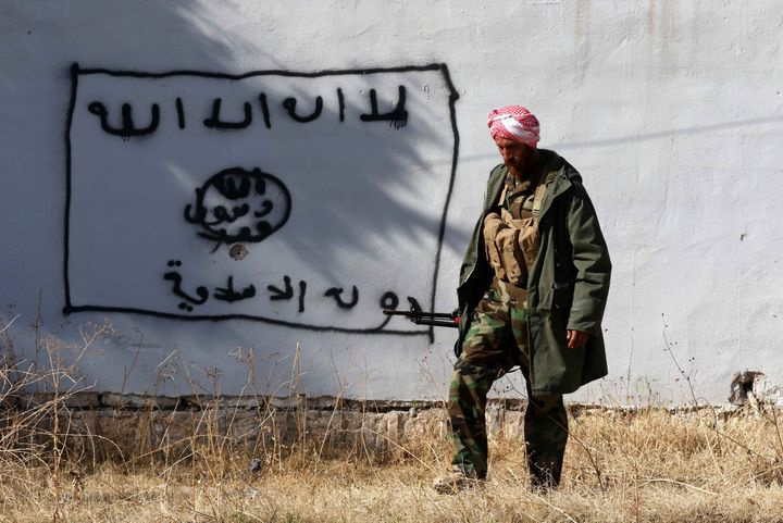 A Kurdish fighter walks by a wall bearing a drawing of the flag of the Islamic State (IS) group in the northern Iraqi town of