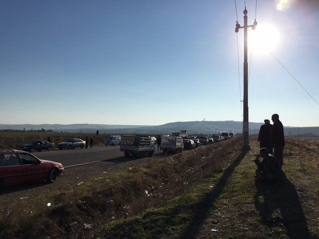 Yazidi men stand on the side of a main road leading to Sinjar, waiting for permission to enter the city that was recently fre