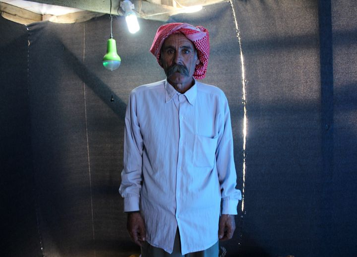 A Yazidi man poses for a photograph in his makeshift shelter in Dayrabun, Iraq, on Nov. 14, 2015.
