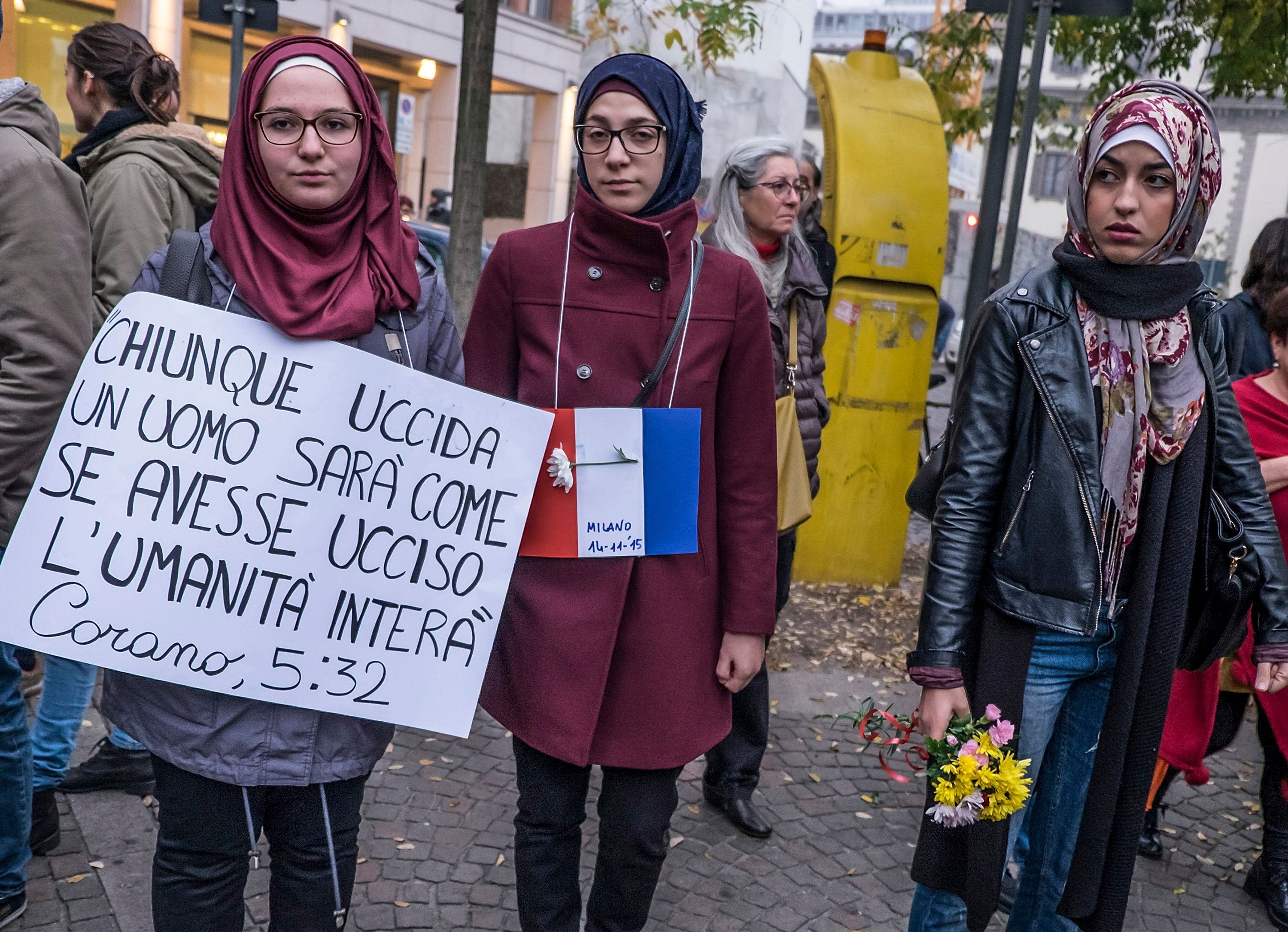 MILAN, ITALY - NOVEMBER 14:  Muslim women hold a sign with a writing from the Coran during the service in the city centre on November 14, 2015 in Milan, Italy. In different cities there have been services to mourn the victims of attacks last night in Paris that left at least 120 people dead across the French capital. The Islamic State (IS) has claimed responsibility for the attacks that were carried out by at least eight terrorist.  (Photo by Awakening/Getty Images)