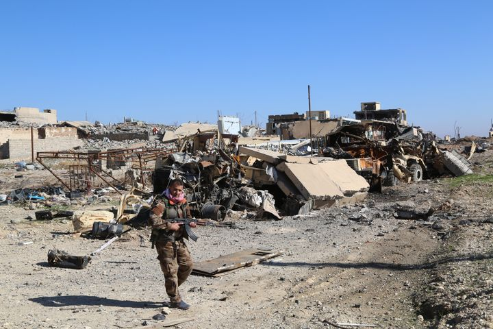 A Peshmerga fighter in front of highly damaged buildings and vehicles after the US-backed Kurdish operation to clear Sinjar o