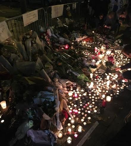 Flowers and candles lines the streets outside the Bataclan in Paris on Saturday.