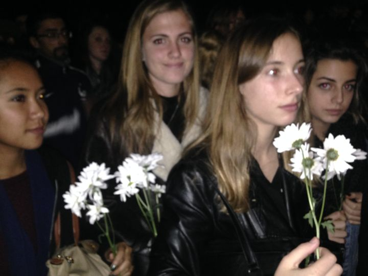 Parriche, in the light jacket, came to the vigil with her classmates, holding flowers.