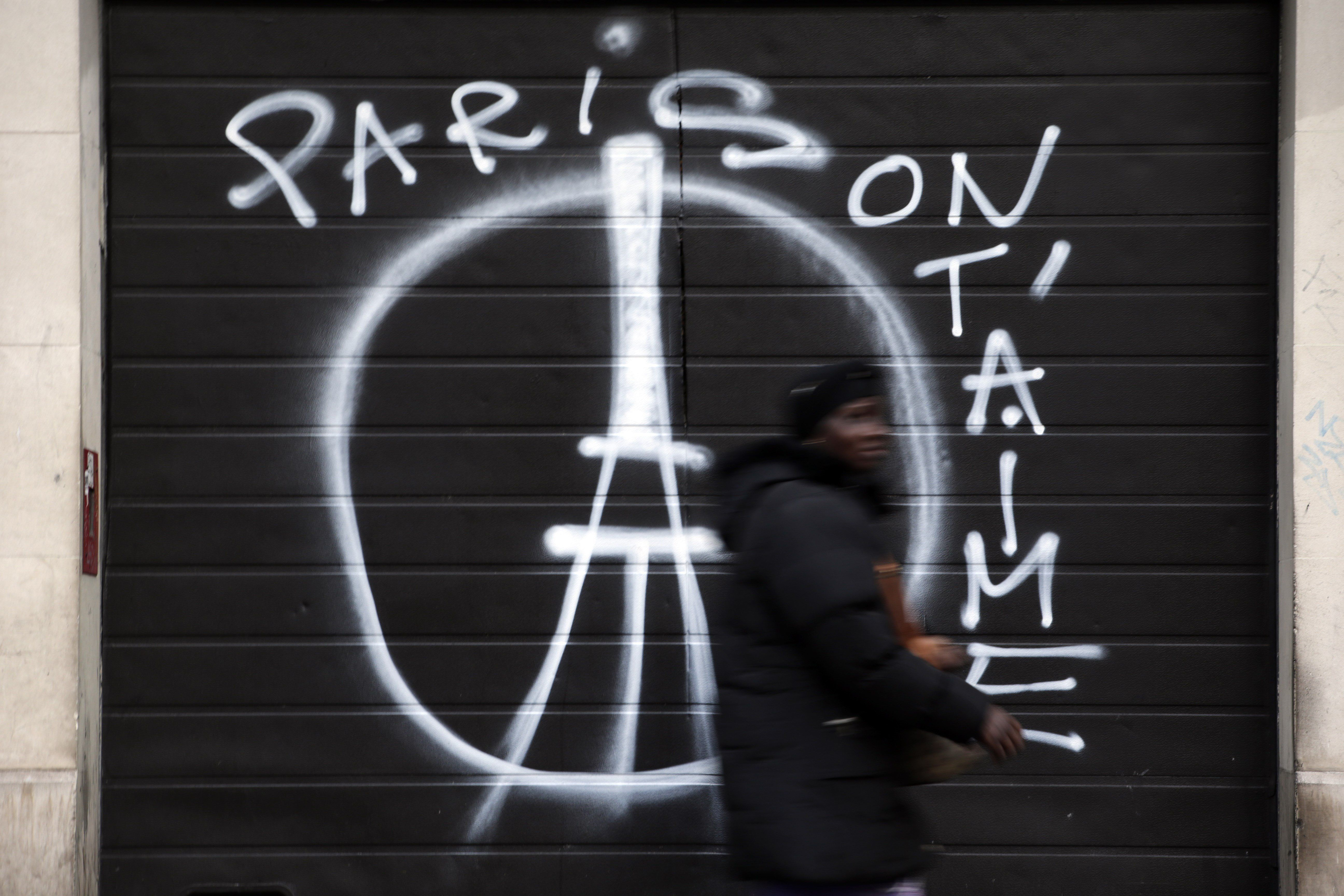 """A woman walks past a shuttered shop with graffiti that reads """"Paris we love you"""" in central east Paris on November 15, 2015."""