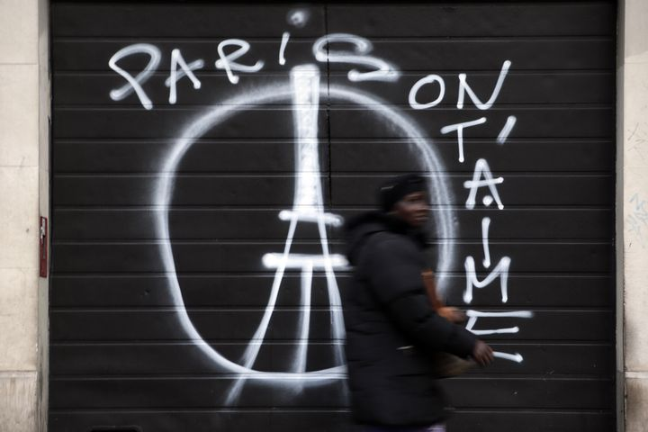 "A woman walks past a shuttered shop with graffiti that reads ""Paris we love you"" in central east Paris on November 15, 2015."