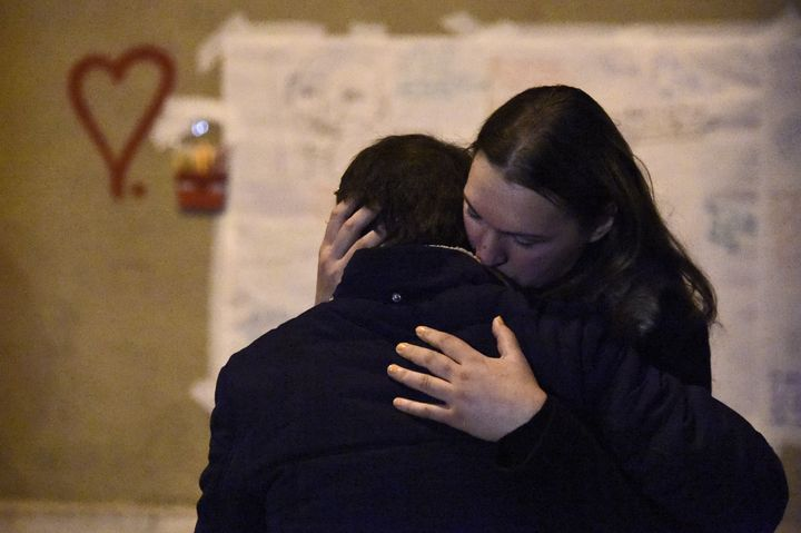 People comfort each other on Sunday during a gathering at a makeshift memorial in front of Le Carillon restaurant in Paris, w