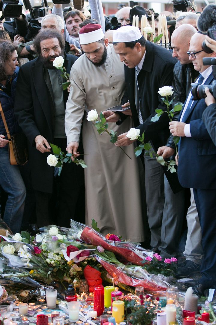 Author Marek Halter (L), Imam Hassen Chalghoumi (3rd from L), and ImamHocine Drouiche (R) gather at a makeshift memoria