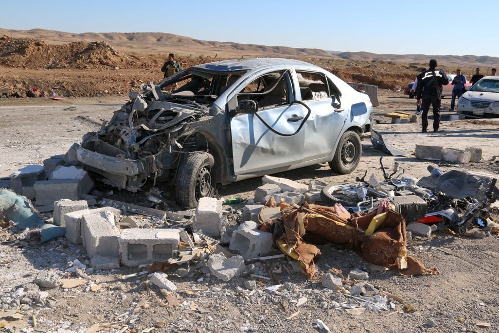 Iraqi men stand next to the wreckage of a car on November 4, 2015, in the aftermath of a suicide bombing by militants of Isla