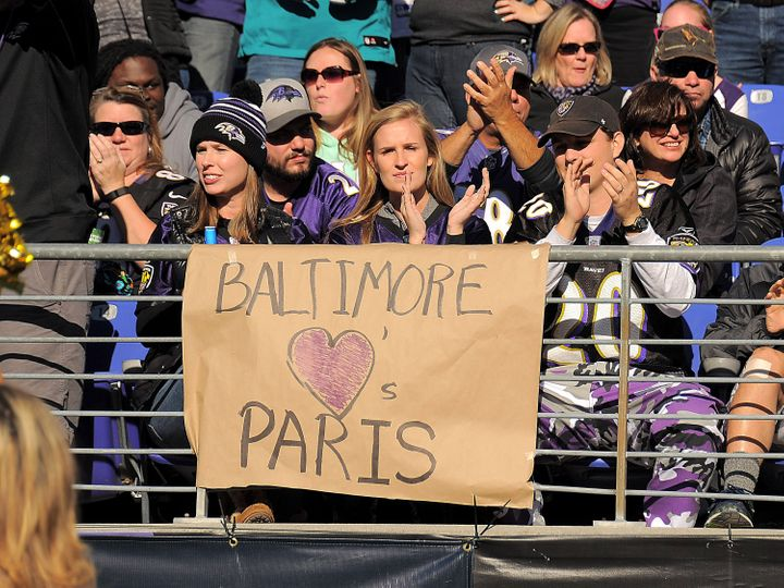 Baltimore Ravens fans (from left) Hannah Keegan, Emma Garman and Terry Keegan display a sign honoringthe victims of the