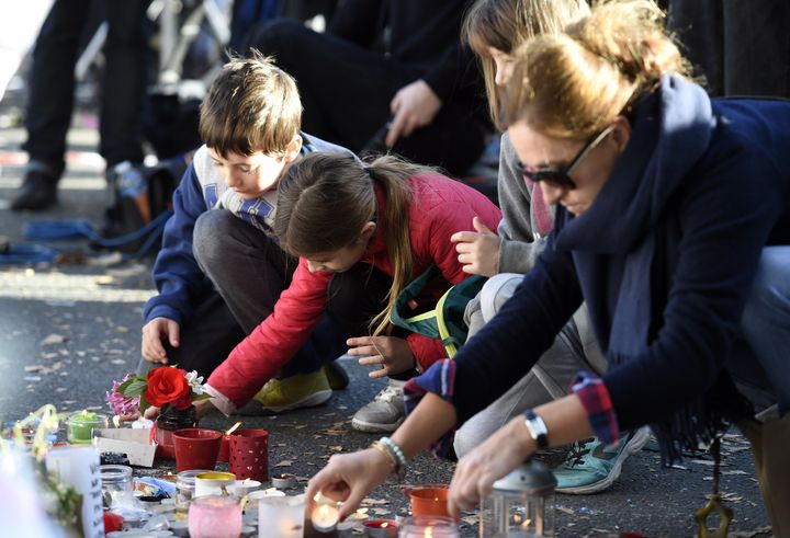 Children and adults lay flowers and light candles at a makeshift memorial along a police cordon set up close to the Bataclan