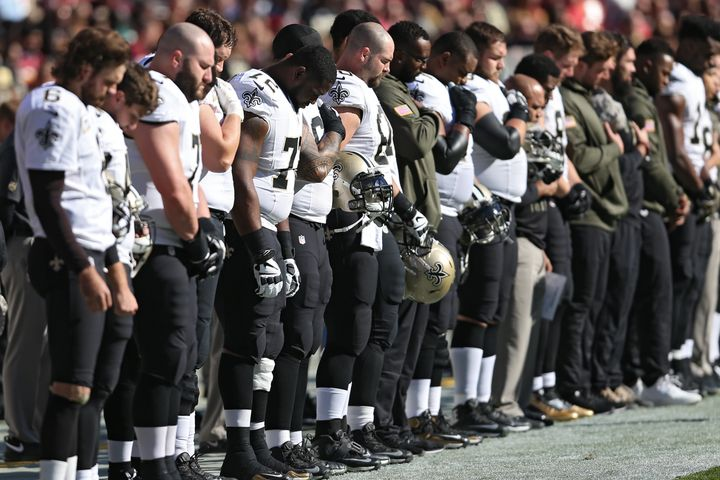 New Orleans Saints players participate ina moment of silence before playing the Washington NFL teamat FedExField&