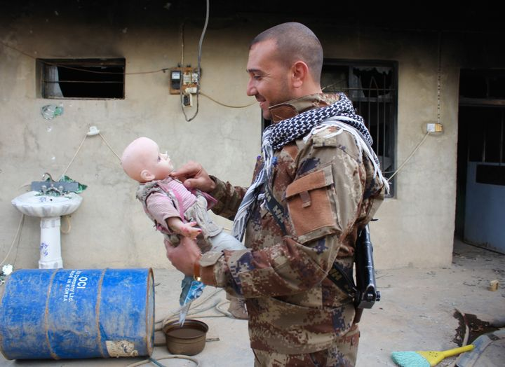 A member of the Asayesh security forces picks up a doll he gave to his daughter. ISIS destroyed his home in Sinjar, Iraq.
