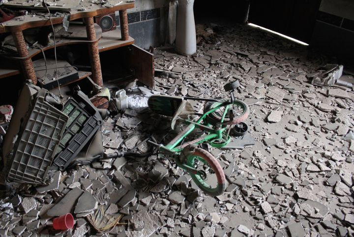 A child's tricycle in the burnt remains of a Yazidi family home in Sinjar, Iraq.