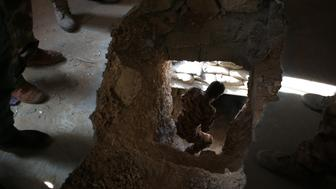 SINJAR, IRAQ - NOVEMBER 15:  A Peshmerga enters a former ISIL tunnel on November 15, 2015 in Sinjar, Iraq. Kurdish forces, with the aid of massive U.S.-led coalition airstrikes, liberated the town from ISIL extremists, known in Arabic as Daesh, in recent days. Daesh used the tunnels to protect against Kurdish attacks. Local Yazidi fighters wo fought with Kurdish forces and some former residents have been taking any salvagable items out of the rubble, the town being uninhabitable and perilously close to the frontline.  (Photo by John Moore/Getty Images)