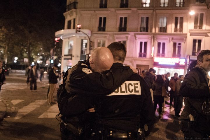Apoliceman buries his head in another policeman's shoulder while in Paris' 11th arrondissement on Sunday, Nov.15,