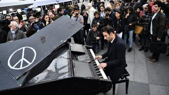 A man plays piano as people gather after observing a minute of silence to pay tribute to victims of the attacks claimed by Islamic State, on November 16, 2015 at the Place de la Republique in Paris. France and other countries in Europe held a minute's silence in memory of the victims of the worst ever terror attacks on French soil. AFP PHOTO / LOIC VENANCE        (Photo credit should read LOIC VENANCE/AFP/Getty Images)