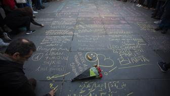 Mourners write messages in chalk as they gather to pay their respects to victims of the terrorist attacks, at Place de la Republique, in Paris, France on Sunday, Nov. 15, 2015. French investigators are still reconstructing how three teams of Islamic State militants killed at least 129 people in coordinated attacks in Paris on Friday. Photographer: Simon Dawson/Bloomberg via Getty Images