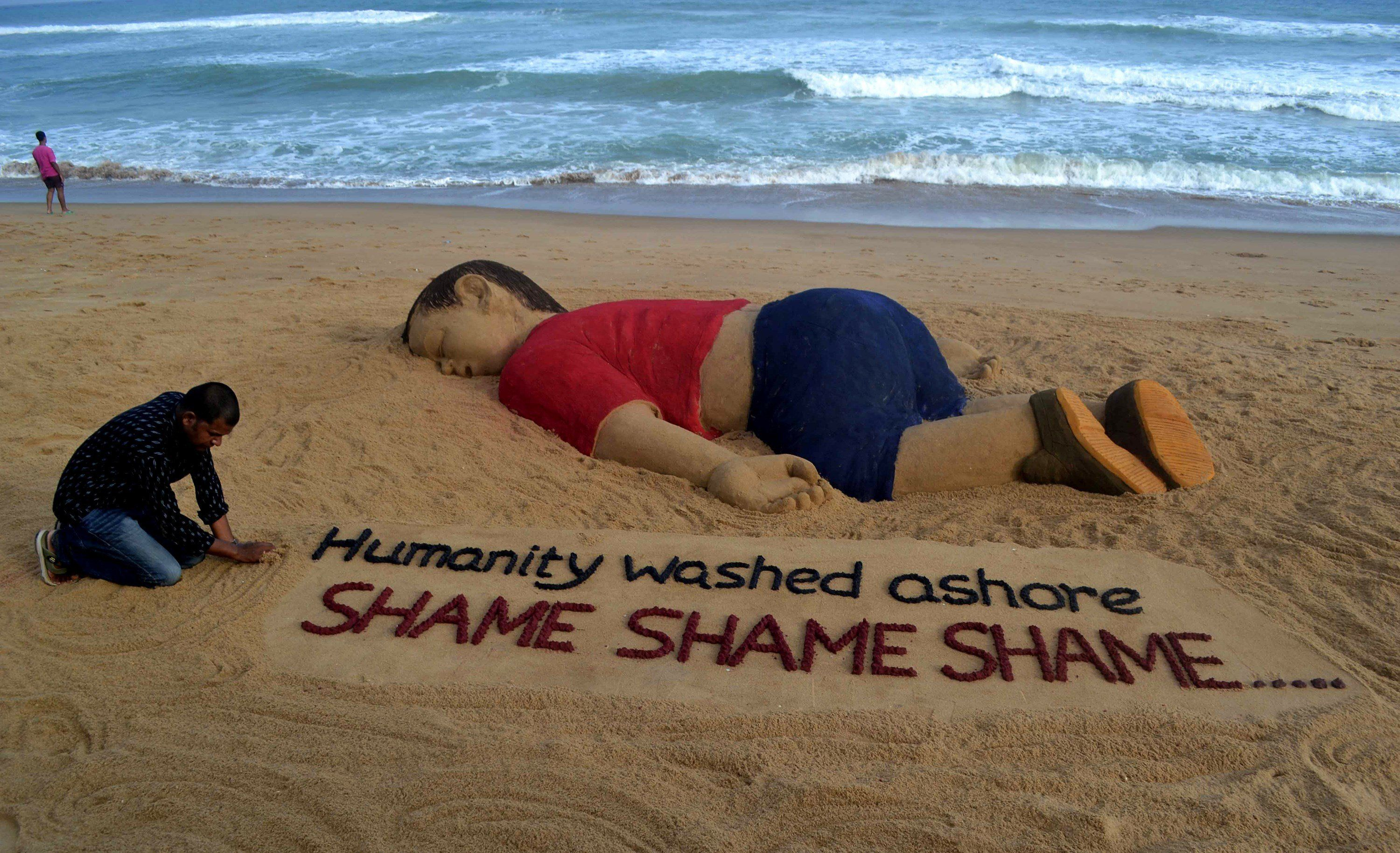RESTRICTED TO EDITORIAL USE, MANDATORY MENTION OF THE ARTIST UPON PUBLICATION, TO ILLUSTRATE THE EVENT AS SPECIFIED IN THE CAPTION Indian artist Sudarsan Pattnaik works on a sand sculpture depicting drowned Syrian boy Aylan Kurdi at Puri beach, some 65 kilometers away from Bhubaneswar, on September 4, 2015. Charities helping refugees saw a surge in donations on September 4 across Europe as people shocked by the heart-rending images of a drowned Syrian boy on a Turkish beach dug deep to help out. The photos of the lifeless body of three-year-old Aylan Kurdi, lying on a beach in Bodrum, Turkey, have triggered a wave of emotion across the continent, despite deep divisions among European governments on how to deal with the crisis.  AFP PHOTO/ASIT KUMAR        (Photo credit should read ASIT KUMAR/AFP/Getty Images)