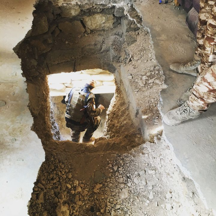 A Yazidi member of the local Asayesh security forces heads down a 65-foot-long ISIS tunnel, dug under a family home in Sinjar