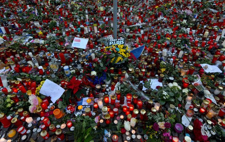 Candles and flowers are placed in front of the French embassy in Prague as part of an international outpouring of grief and s