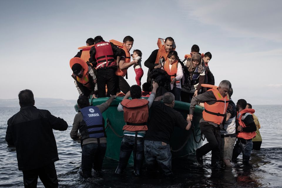 A man is helping out a baby as refugees from Afghanistan and Syria disembark from in a life boat on the shores of Lesbos near