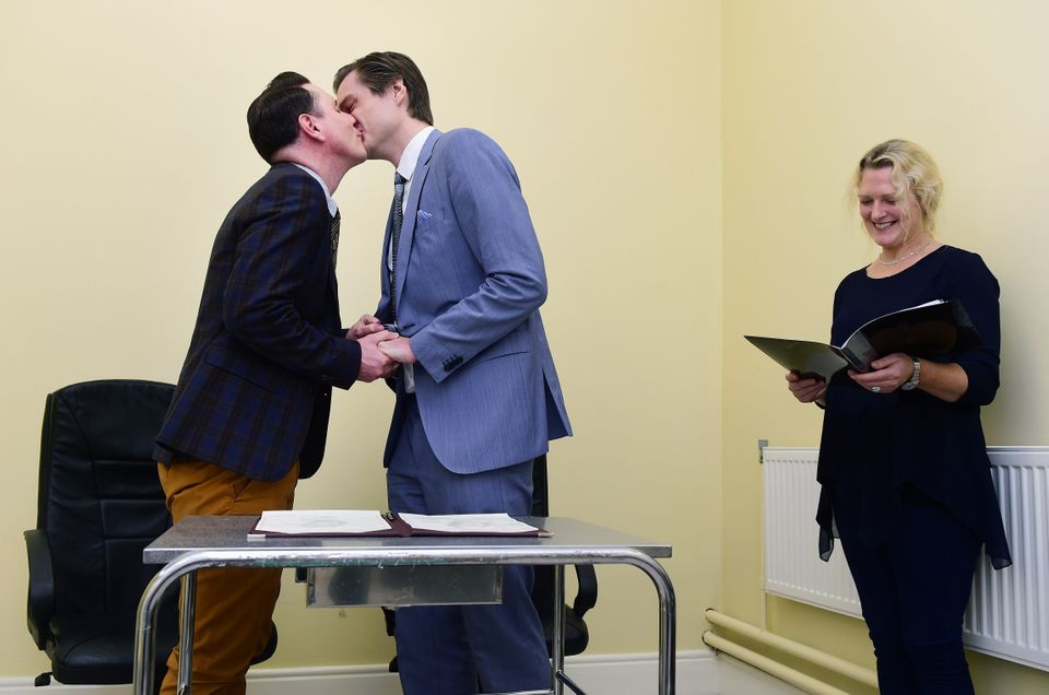 DUBLIN, IRELAND - NOVEMBER 17: Newly married couple Richard Dowling (L) and Cormac Gollogly (2nd L) kiss next to registrar Ma