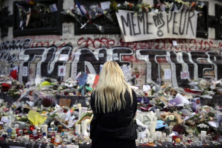 A woman stands in front of a makeshift memorial made up with flowers, candles and messages, on November 17, 2015, at the Plac