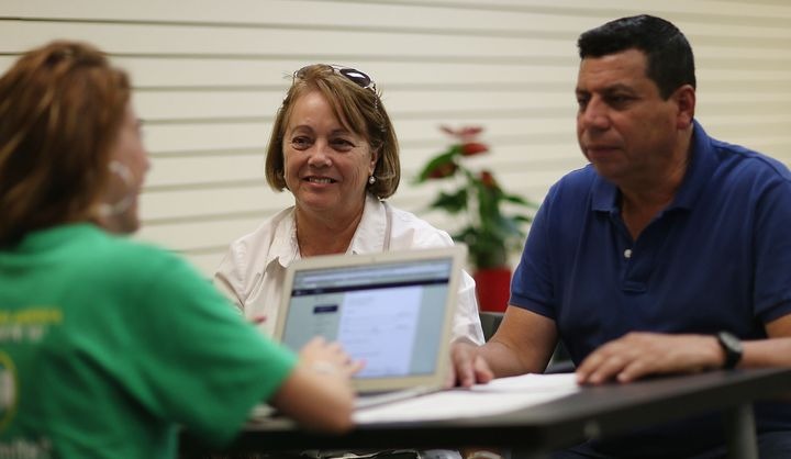 Elvira Lopezto (center) and Pedro Salavarria Carrasco (right) speak with an insurance agent from Sunshine Life and Health Adv