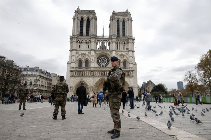 Soldiers patrol in front of the Notre Dame Cathedral on November 16, 2015 in Paris, ahead of a momentof silence for vic