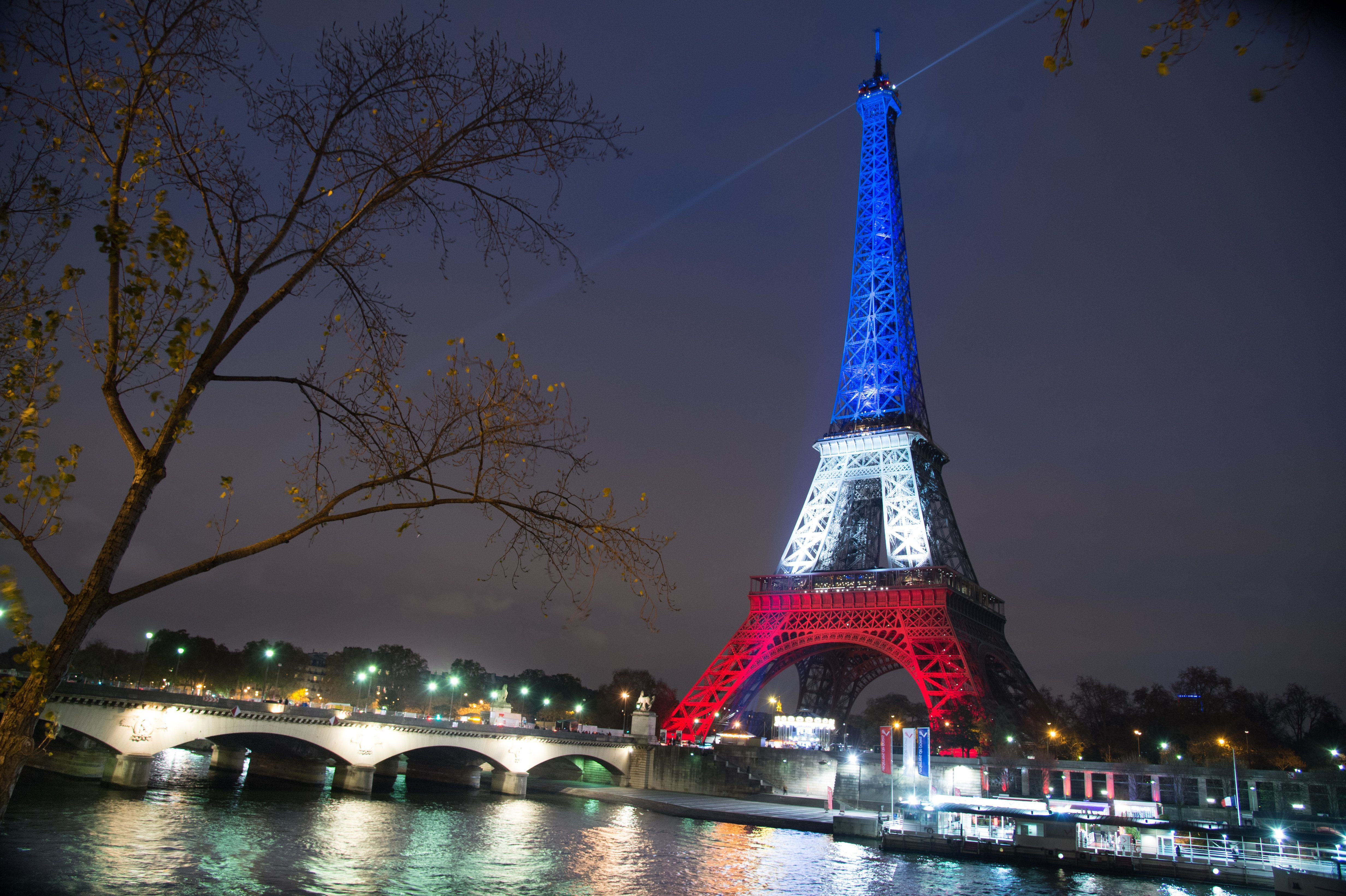 PARIS, FRANCE - NOVEMBER 16:  The Eiffel Tower is illuminated in Red, White and Blue in honour of the victims of Friday's terrorist attacks on November 16, 2015 in Paris, France. Countries across Europe joined France today to observe a one minute-silence in an expression of solidarity with the victims of the terrorist attacks, which left at least 129 people dead and hundreds more injured on November 16, 2015 in Paris, France.  (Photo by Thierry Orban/Getty Images)