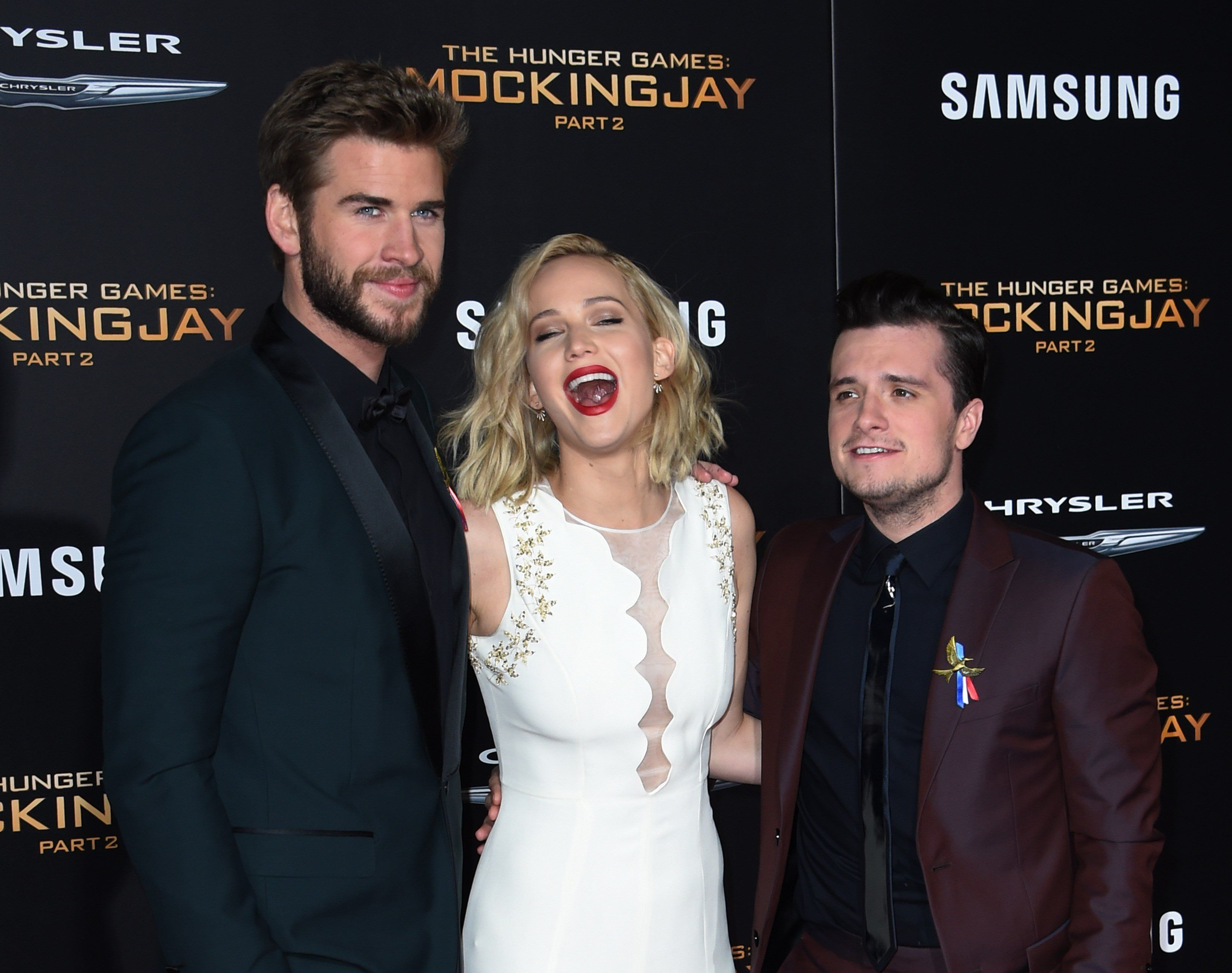 Actors (L-R) Liam Hemsworth, Jennifer Lawrence and Josh Hutcherson arrive for the premiere of Lionsgate's 'The Hunger Games: Mockingjay - Part 2' at Microsoft Theater in Los Angeles, California on November 16, 2015.                AFP PHOTO/MARK RALSTON        (Photo credit should read MARK RALSTON/AFP/Getty Images)