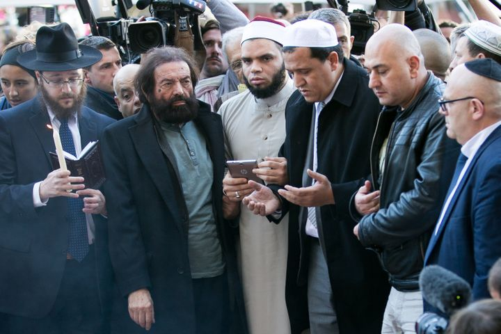 French imams join Jewish leaders outside the Bataclan theater to mourn and sing the French national anthem on Sunday, Nov. 15