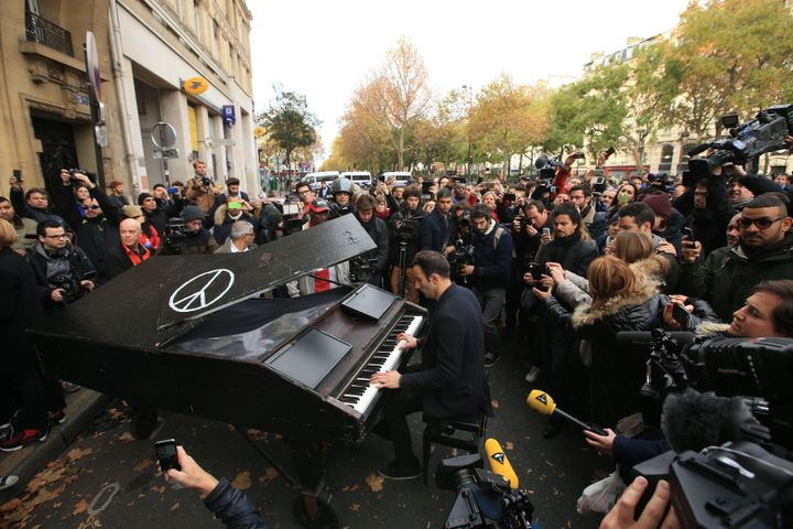 An unnamed man brings his portable grand piano and plays John Lennon's Imagine by the Bataclan, Paris.