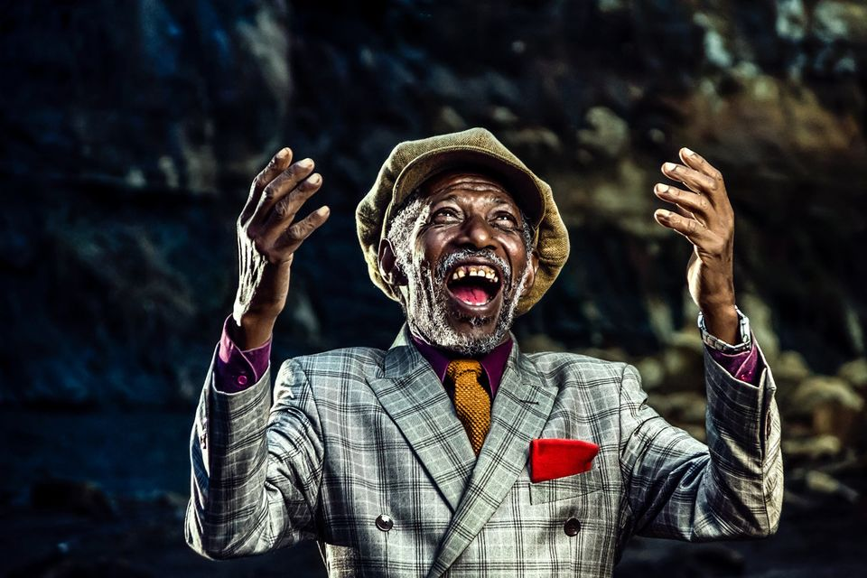 Old smartly dressed man laughing towards the heavens after some good fortune.