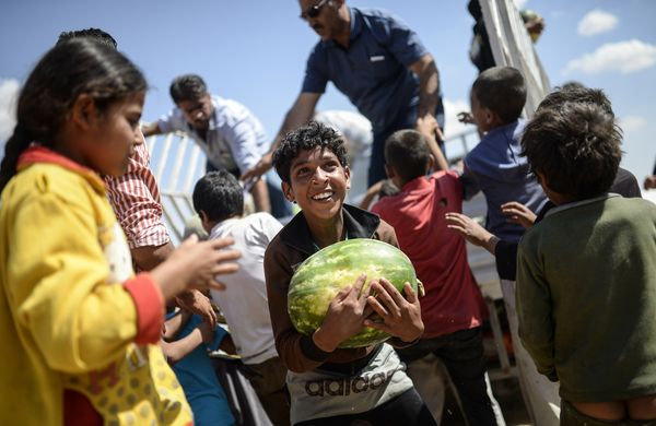 A Syrian child holds a watermelon, one of several distributed near the Akcakale crossing gate between Turkey and Syria at Akc