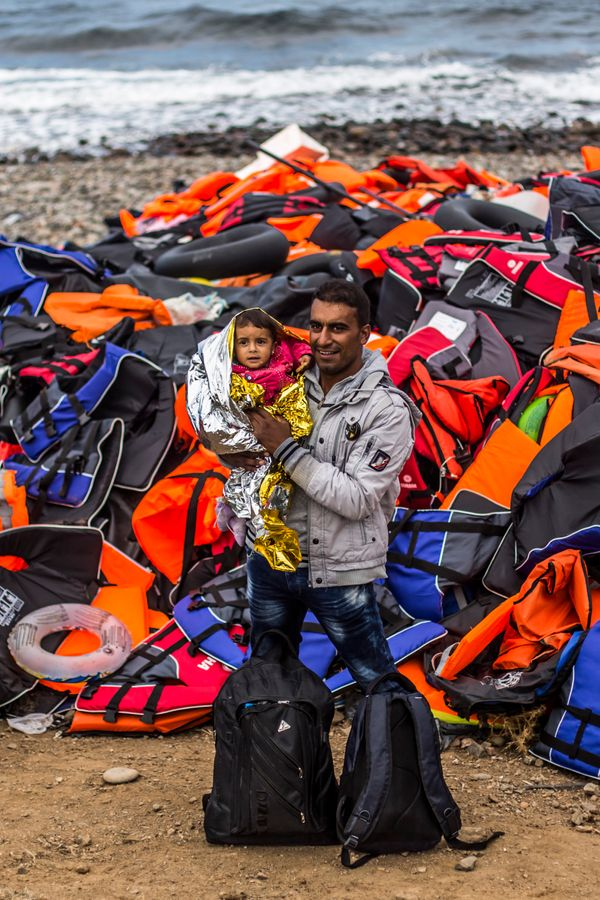 A man from the Syrian town of Aleppo poses with his child in front of a mound of life jackets on the Greek island of Les
