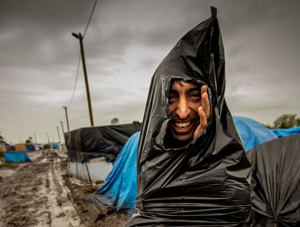 "A refugee, using a plastic trash bag to protect himself from the rain, walks through the ""New Jungle"" migrant camp in Calais,"