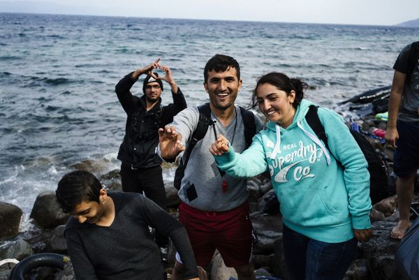 Mahmud, 28, and his bride, Firal, 25, both from the Syrian city of Kobane, show their rings as they arrive with other refugee