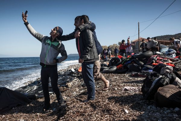 Refugees from Afghanistan and Syria take selfies after arriving in boats on the shores of Lesbos on Nov. 2, 2015, near Molyvo